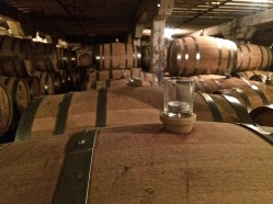 Basalt walls, wine barrels and a wall of library wines at Barrister Winery in Spokane Washington.