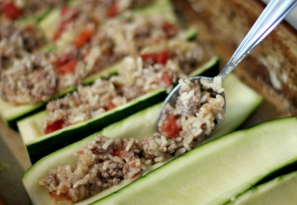 Fill zucchini with rice, ground beef and tomatoes