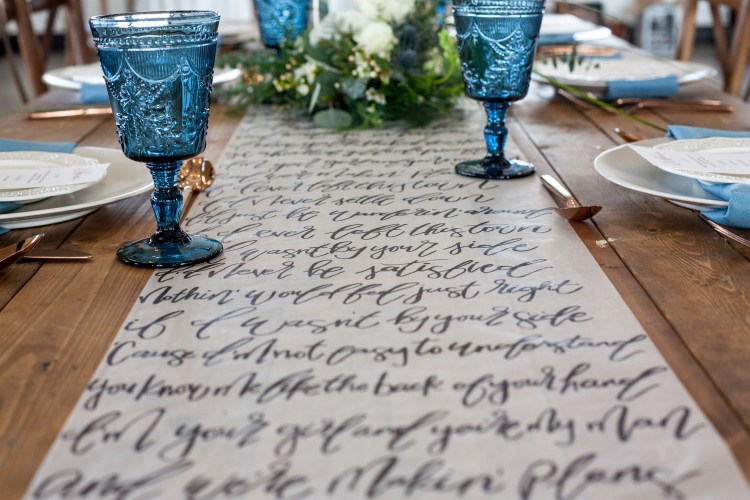 """This piece has to be my favorite piece I have ever made for a styled shoot. When Stacie asked me to be a part of this shoot, she said, """"I have a crazy idea and I think you can do it."""" Her crazy idea was a 10 foot long paper table runner with Miranda Lambert's song """"Makin' Plans"""" hand lettered on it. I hesitantly agreed to try and honestly wasn't sure how I was even going to put it together. I laid out the paper on the floor of my house, taped it down and was quick to shoo my two cats away when they wanted to walk all over it. I penciled in all the lettering, then with a sharpie marker, I went to town. After 8 hours on the floor and a very sore back, this monster of a project was done. I absolutely love the way it turned out and so did everyone else. In case you're interested, yes I offer these on my wedding price sheet. I can make one of these for your wedding using your favorite song or your vows. This is a great way to make your wedding details sweet and personal!"""