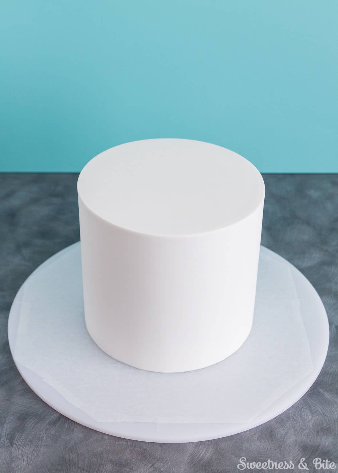 A six inch round cake covered in white fondant icing.