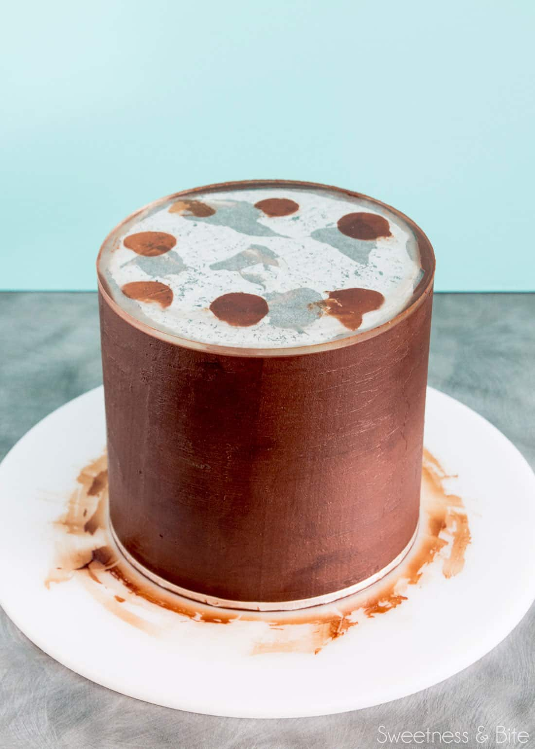 A cake being covered in ganache using an acrylic ganache board.