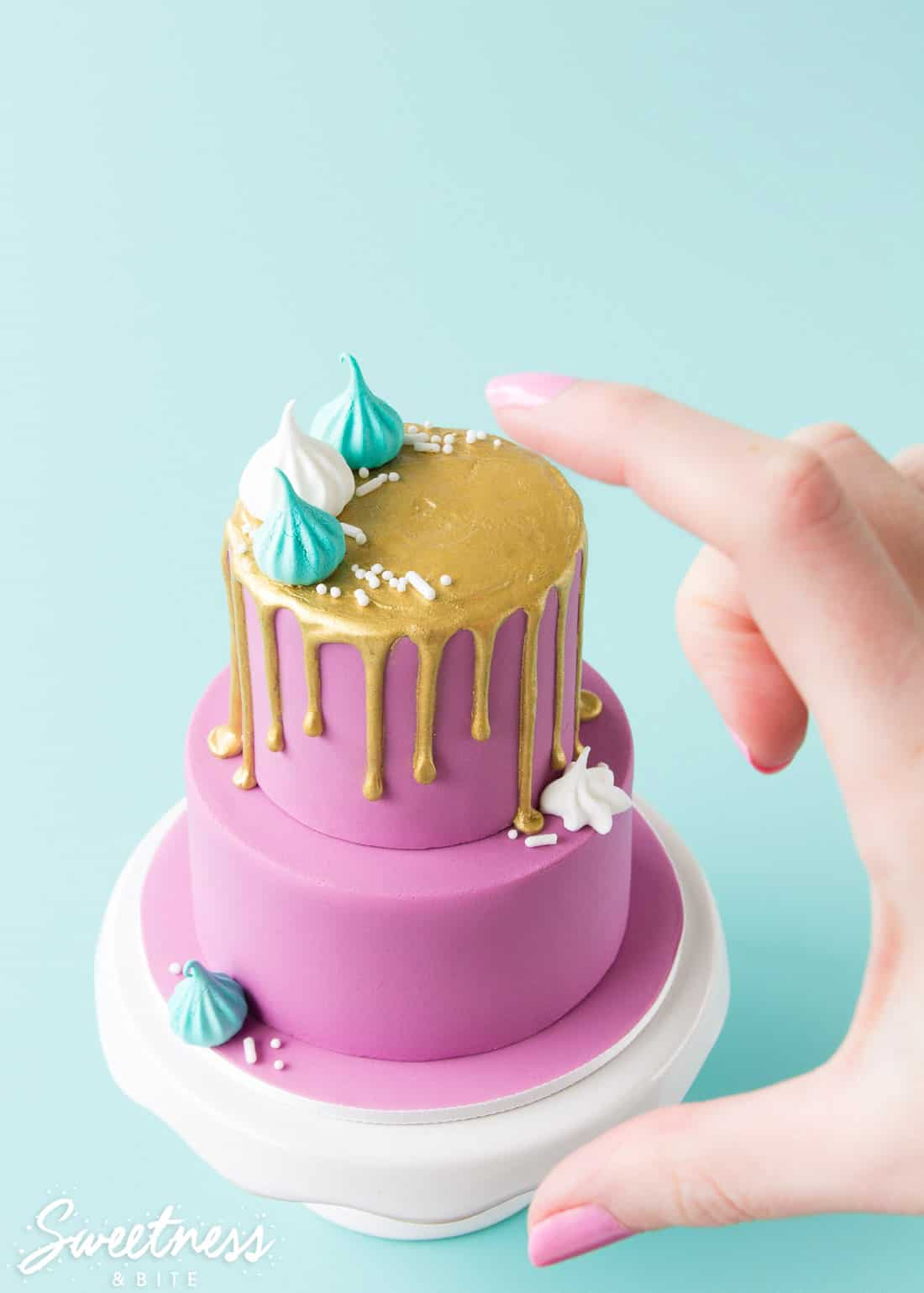 A two tier mini cake with purple fondant and a gold drip, decorated with white and teal mini meringues and white sprinkles. A hand is in the picture so show how small the cake is.