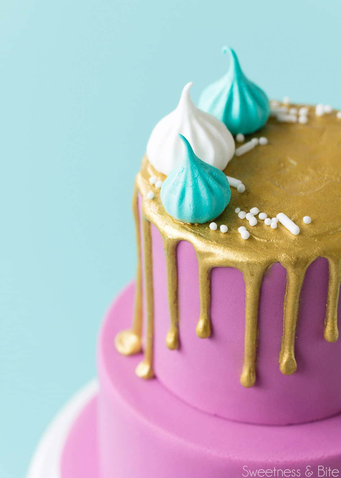 Close up of the top tier of the mini cake, with the gold drip and decorated with white and teal mini meringues and white sprinkles.