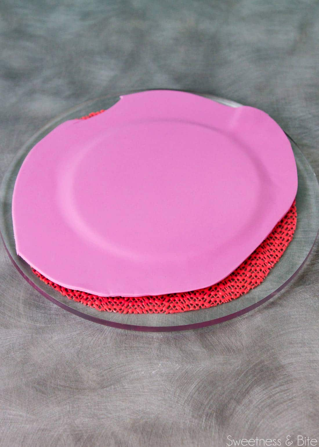 Purple fondant covering a small round cake card.