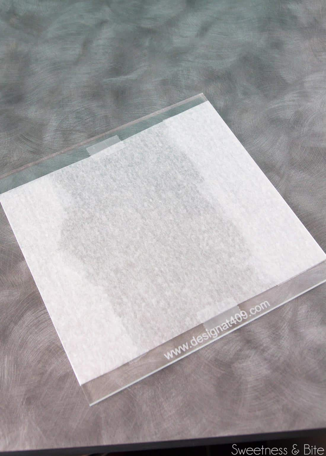 A clear acrylic cake board with a piece of waxed paper taped to it.