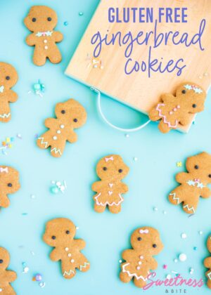Gluten free gingerbread men and women cookies decorated with pastel royal icing, on a blue background.