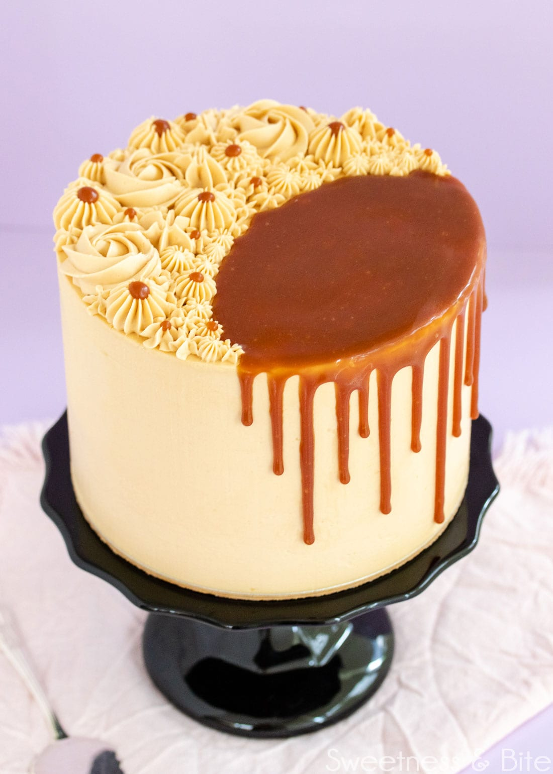 Caramel mud cake on a black cake stand, decorated with swirls of caramel buttercream on top, and a caramel sauce drip.