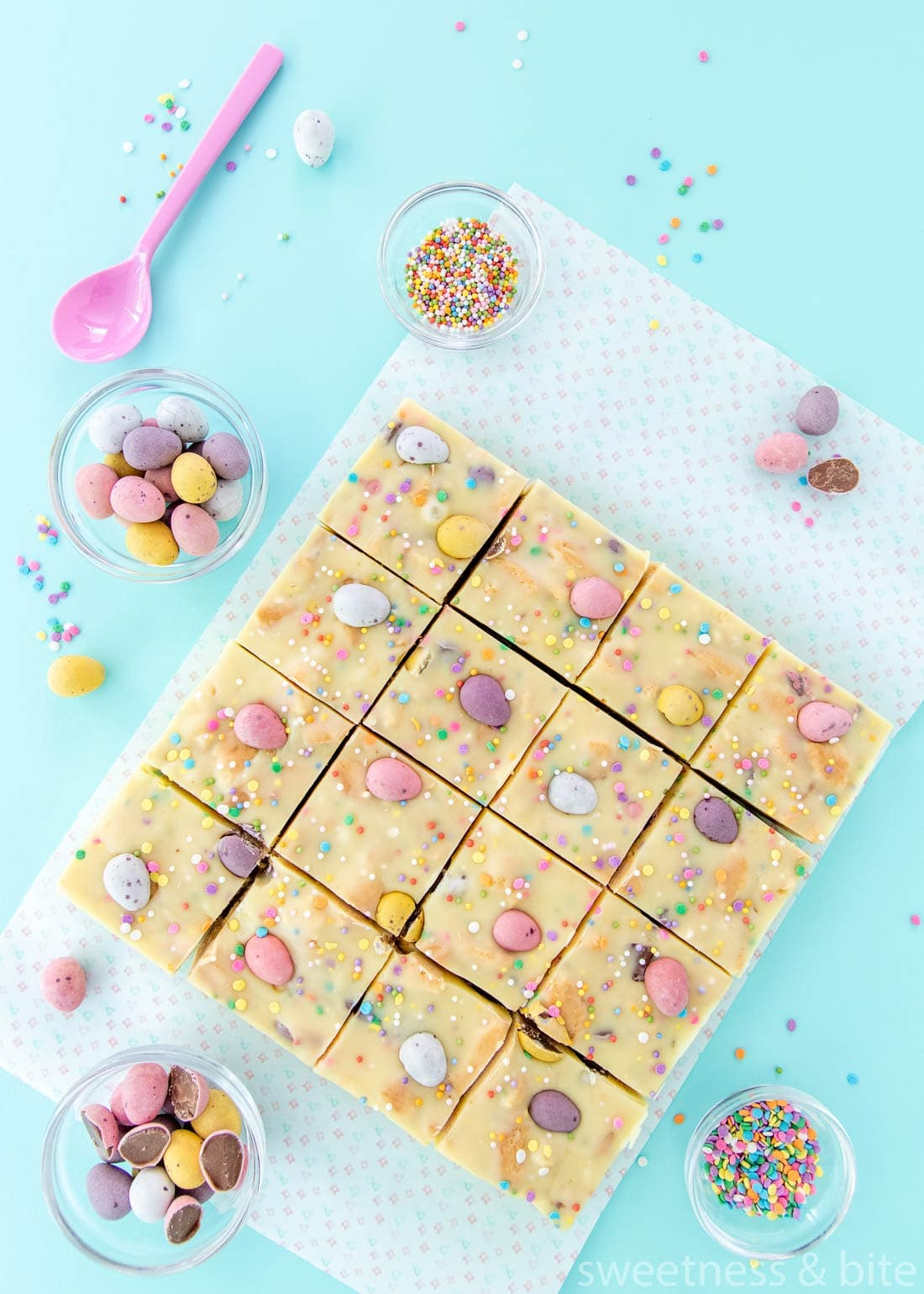 Mini egg fudge slice cut into 16 squares, with sprinkles and mini eggs on a pale blue background.