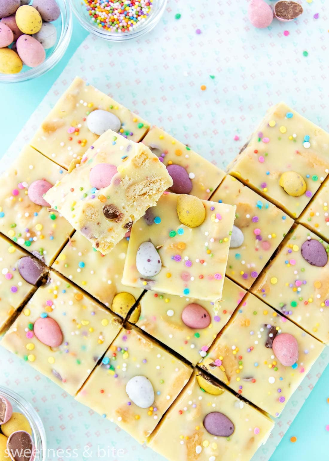 Two squares of mini egg fudge stacked up, showing the cookie pieces inside.