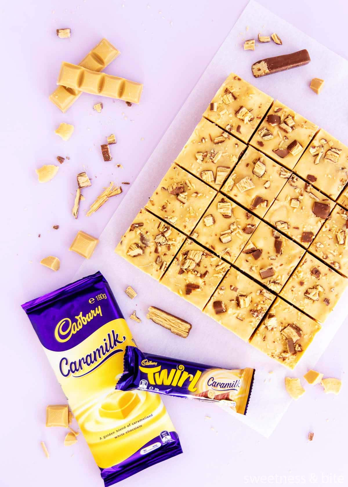 16 squares of Caramilk Fudge Slice, with a wrapped block of Caramilk chocolate and a Caramilk Twirl.