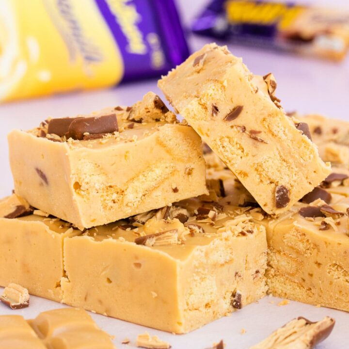 two squares of Caramilk Fudge Slice, stacked on other squares of slice