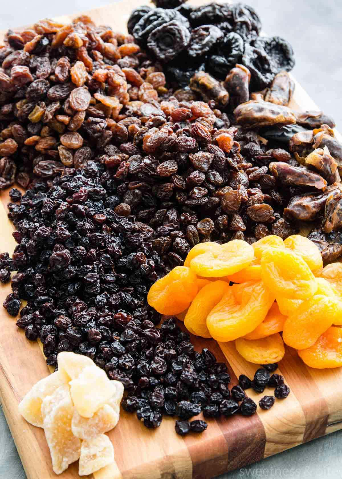 Dried fruits - sultanas, raisins, dates, prunes, currants, apricots and glace ginger - on a wooden board.