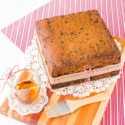 gluten free fruit cake on a wooden board, with a small glass jug of brandy and a pastry brush.