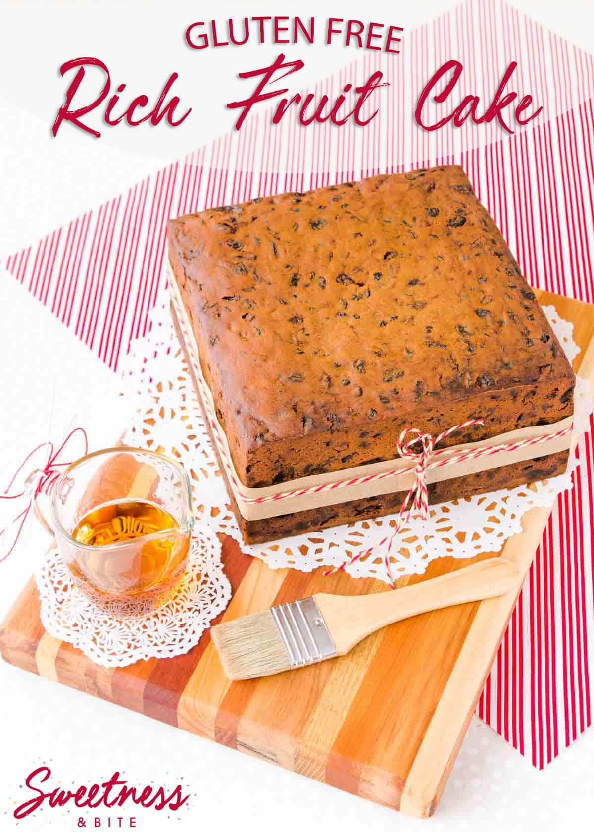 Square gluten free fruit cake on a wooden board, sitting on a red and white striped cloth, with a glass jug of brandy and a pastry brush