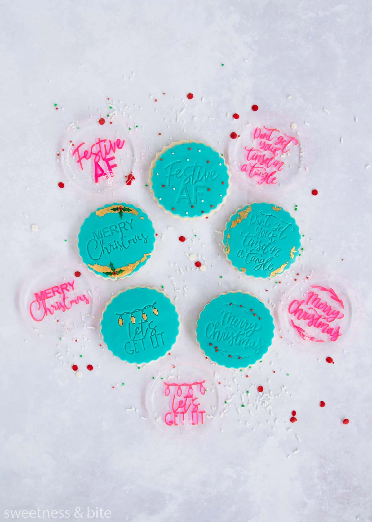 Round cookies decorated with teal fondant circles embossed with messages - Festive AF, Don't get your tinsel in a tangle, Merry Christmas and Let's get lit.