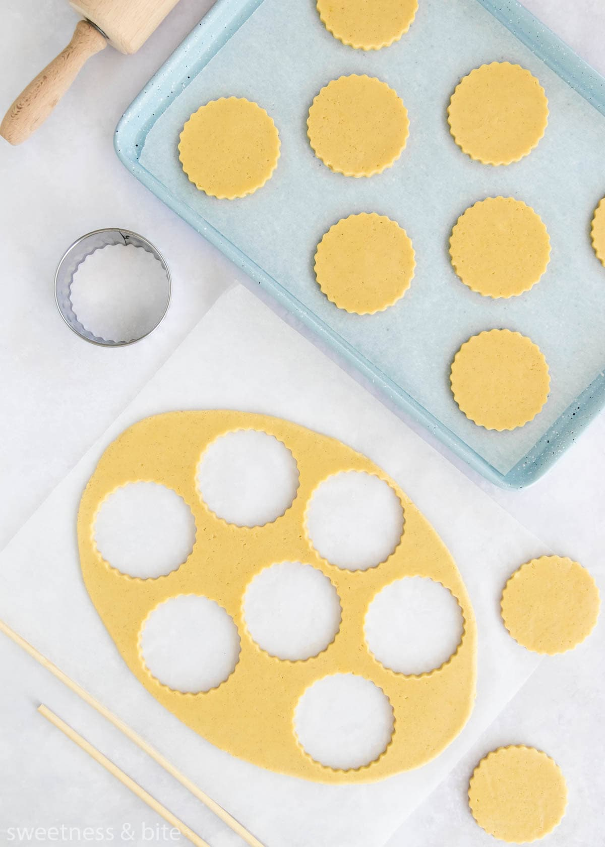 Rolled out cookie dough with scalloped circle shaped cookies cut out.