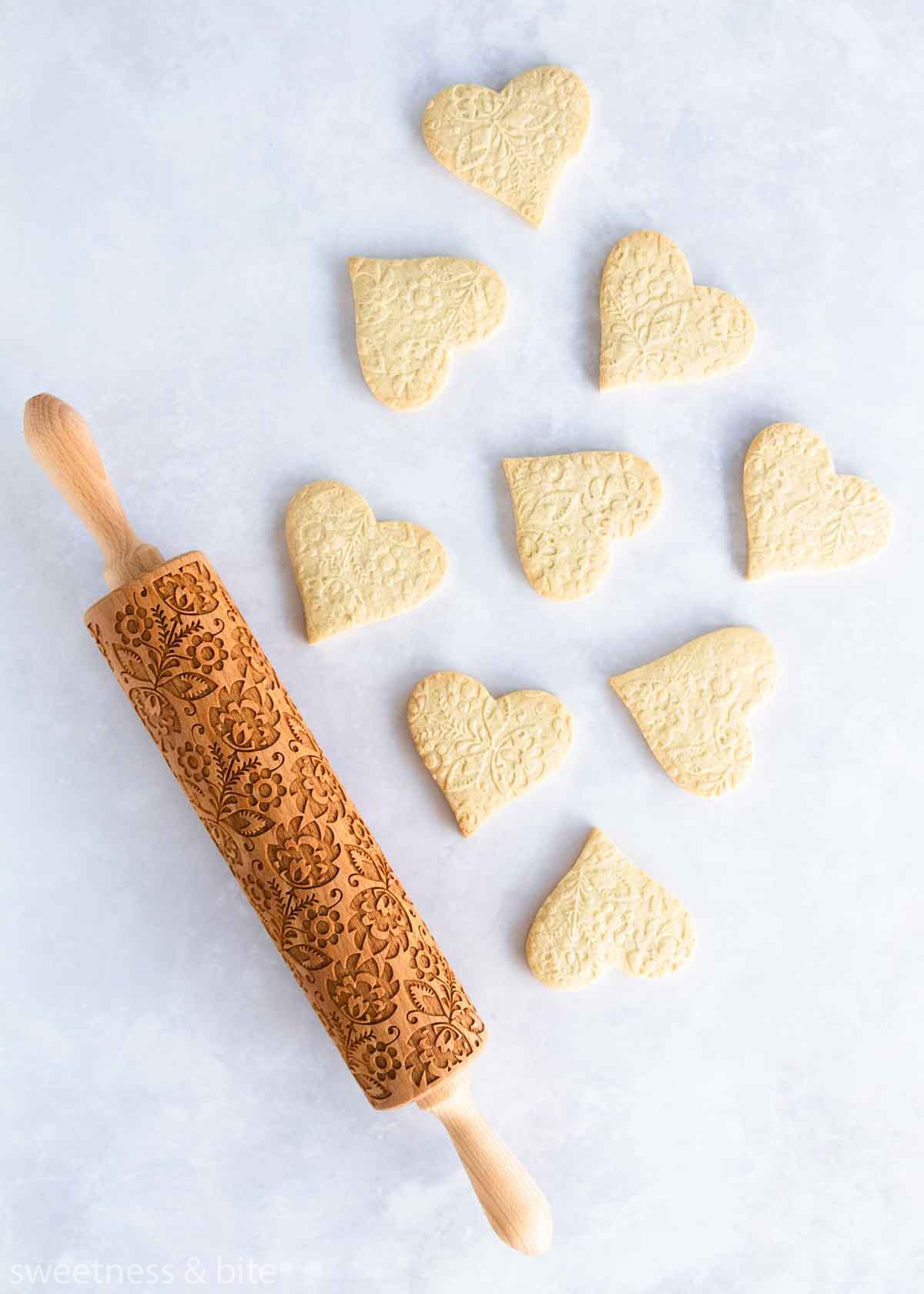 Heart shaped cookies embossed with a floral pattern, with the embossing rolling pin.