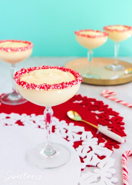 Easy peppermint mousse in a cocktail glass with crushed candy canes around the rim.
