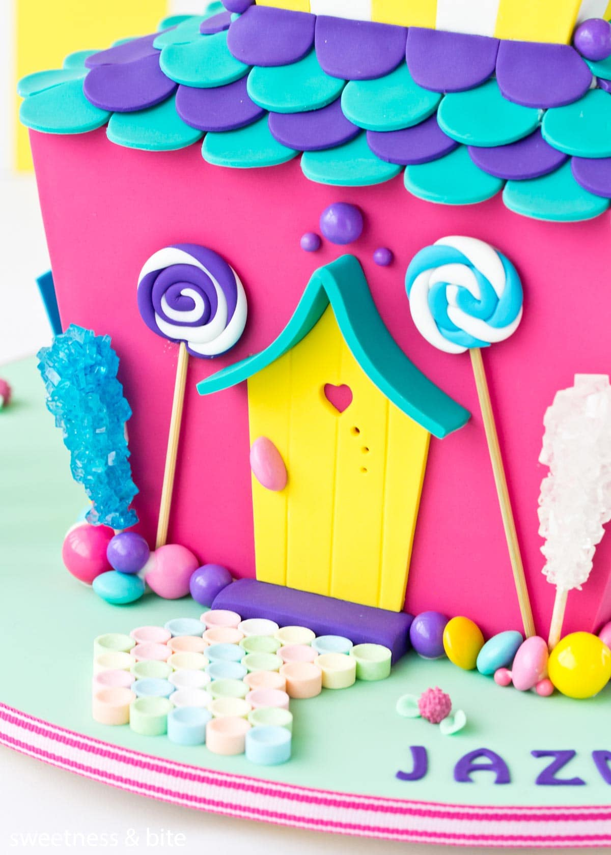 Close up of a candy house cake with a border of assorted lollies attached with royal icing around the bottom of the cake