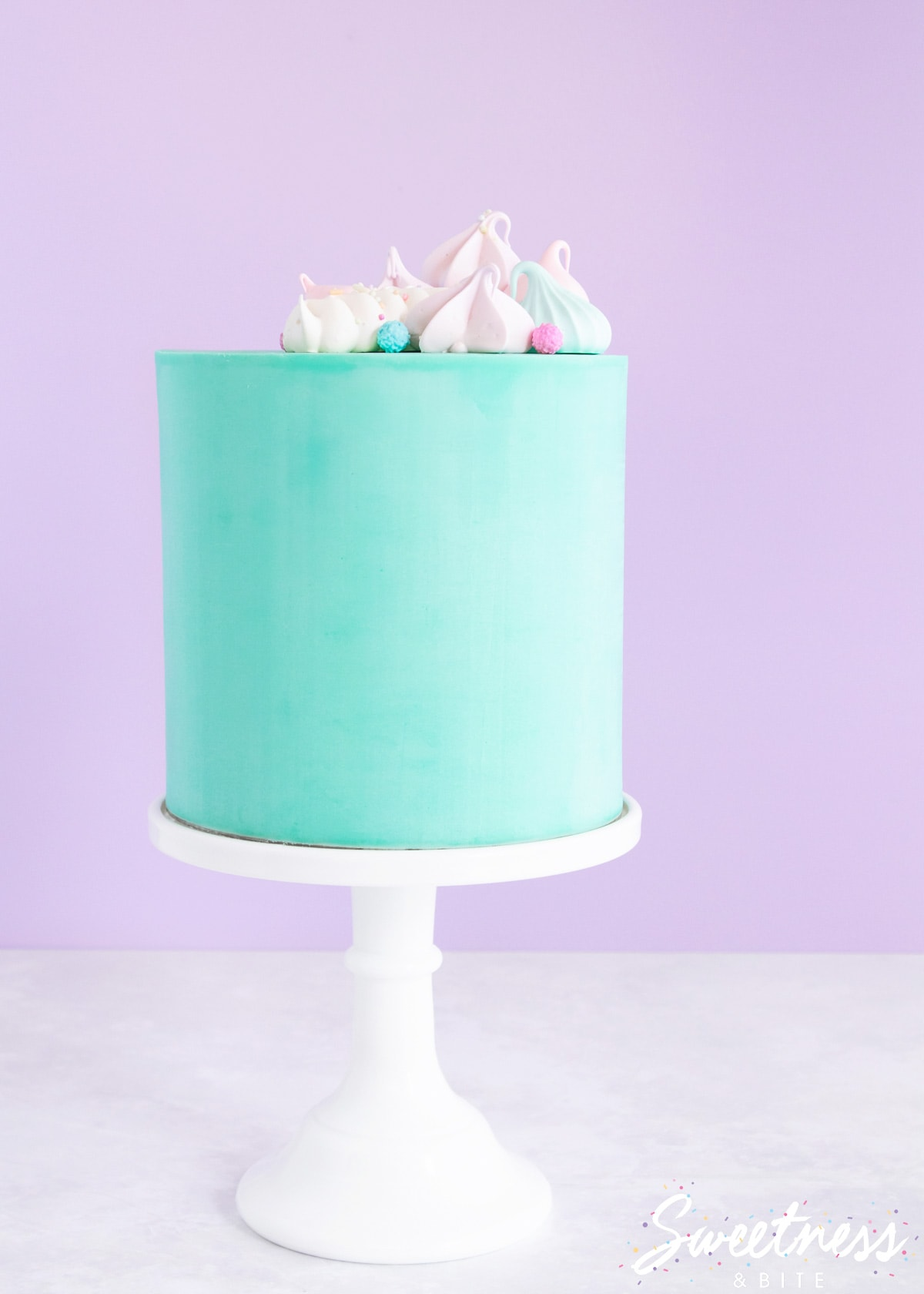 A cake covered in teal ganache on a white cake stand, topped with pastel coloured meringues.