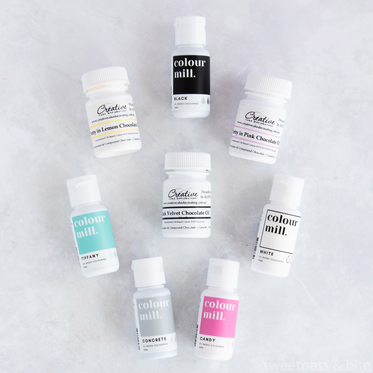 Bottles of Colour Mill and Creative Cake Decorating oil-based food colourings on a pale grey background.