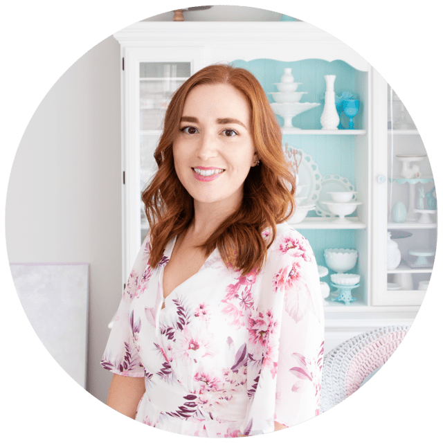 A photo of Natalie, a rather pale redhead in a floral jumpsuit, standing in front of a white-painted hutch dresser displaying cake stands.