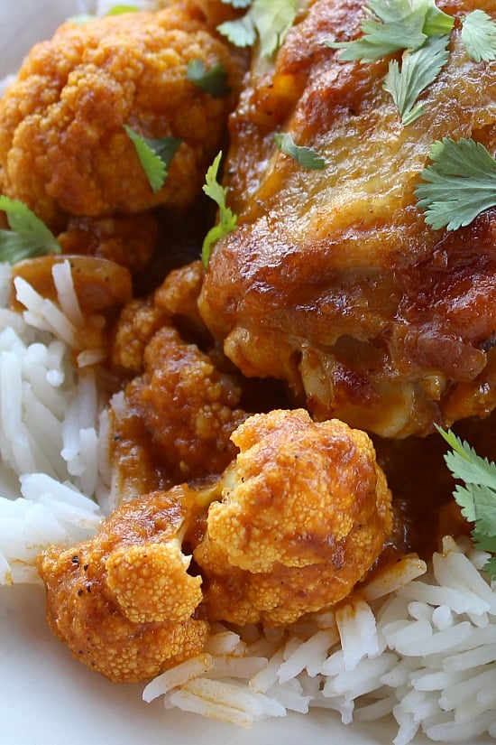 Cauliflower covered in curry sauce next to crispy-skinned chicken.