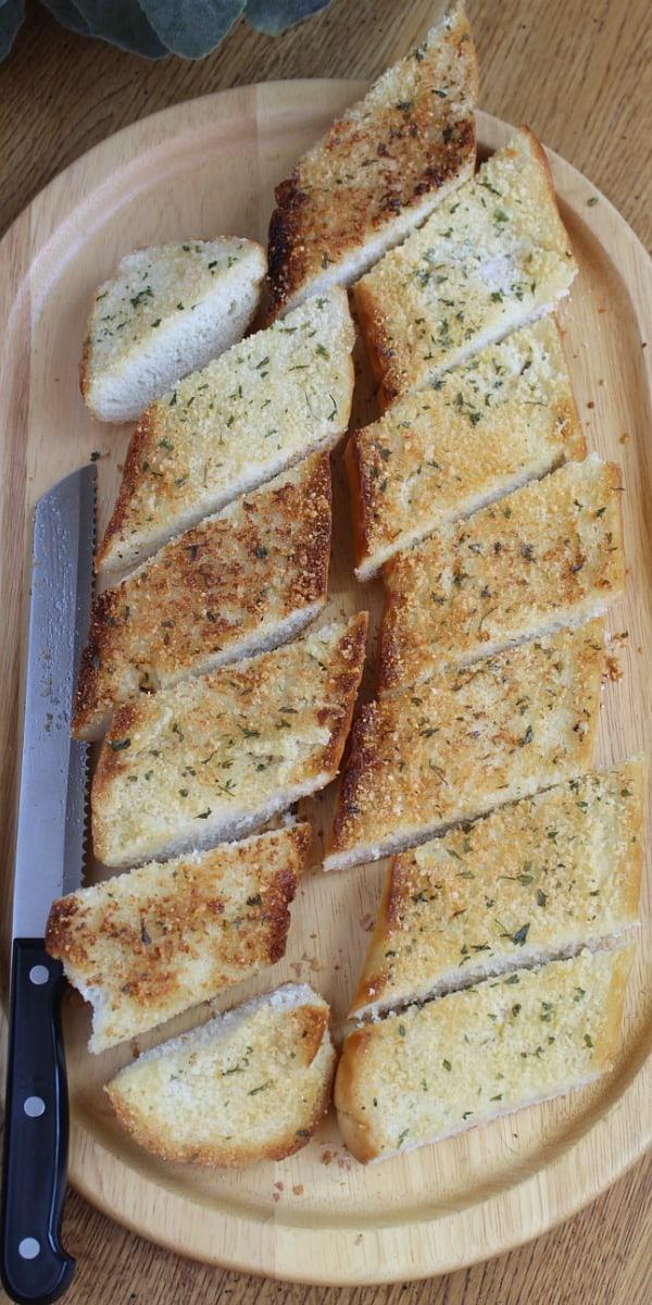 Sliced garlic toast on cutting board.