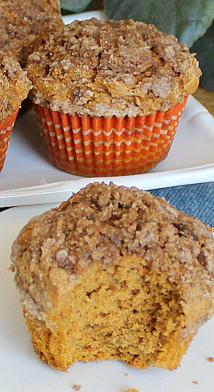Two Pumpkin Streusel Muffins, one with a bite taken.