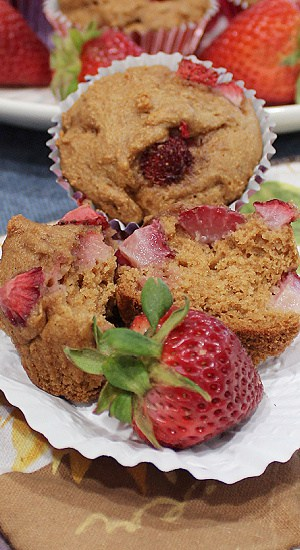 Muffin in half showing chunks of strawberry in the batter.