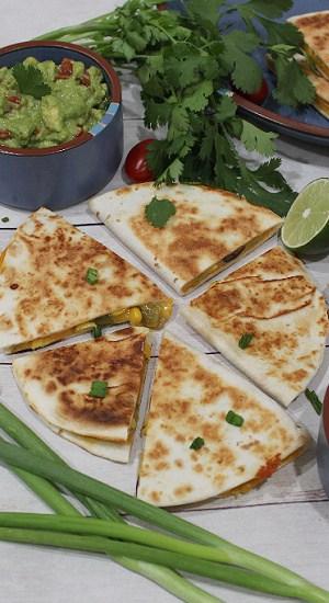 Fresh veggies around a cut quesadilla with a side of guacamole.