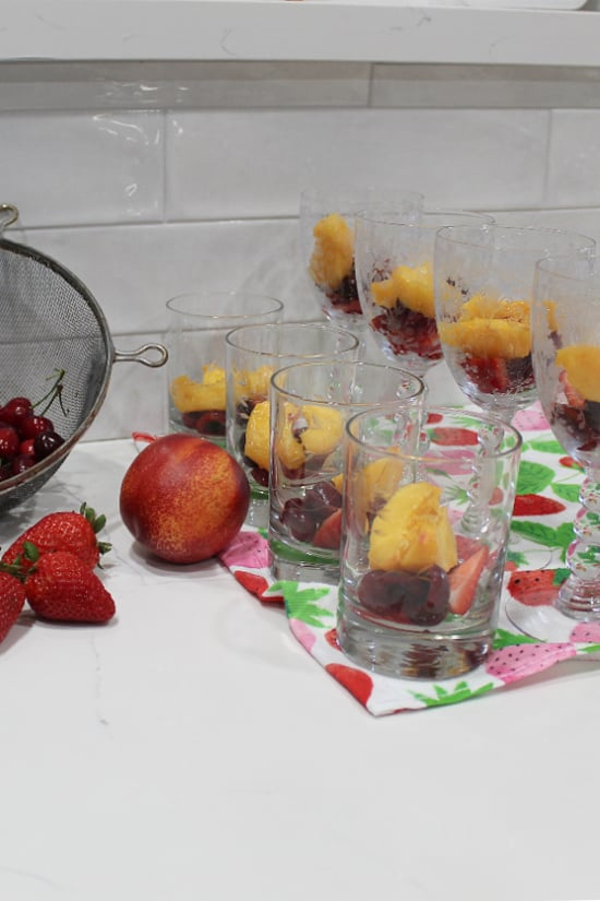 Fresh fruit in clear glasses waiting for the gelatin to be poured in.