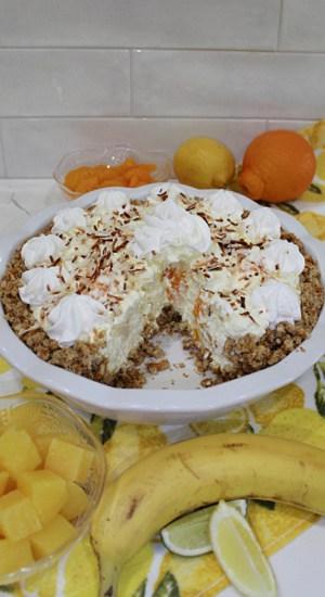 Inside of a pie showing chunks of tropical fruit like pineapple and mandarin orange.