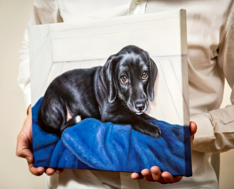 A pair of hands holding an oil painting of a black puppy