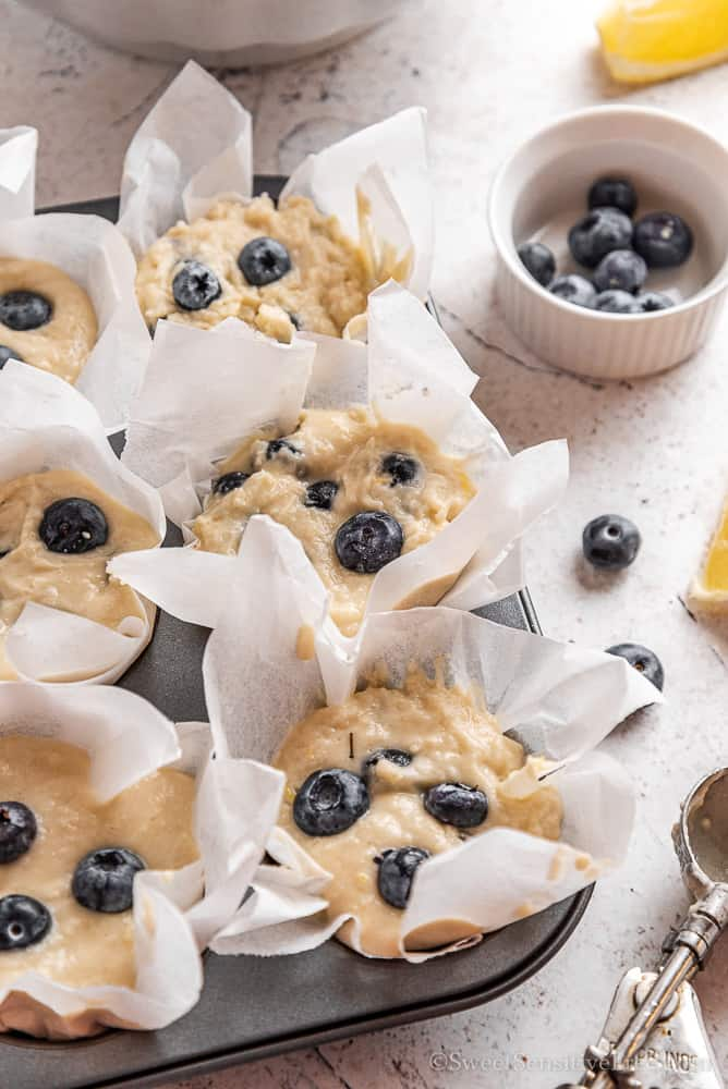 muffin liners filled with blueberry muffin batter