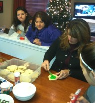 My cousin Juli and her daughter Madison look on as my sister decorates sugar cookies
