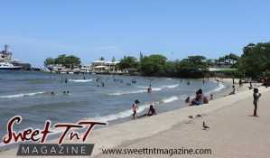 Blue sky, trees, shoreline, Beach, people bathing in water, children on sand, boats in water in Sweet T&T, Sweet TnT Magazine, Trinidad and Tobago, Trini, vacation, travel Chaguaramas Boardwalk