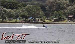 Jet ski in sea water, spectators on shore, trees, at Chaguaramas Beach in Sweet T&T, Sweet TnT Magazine, Trinidad and Tobago, Trini, vacation, travel Chaguaramas Boardwalk