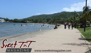 People walking on shore, mountains, blue sky, people bathing in sea water at Chaguaramas Beach in Sweet T&T, Sweet TnT Magazine, Trinidad and Tobago, Trini, vacation, travel Chaguaramas Boardwalk