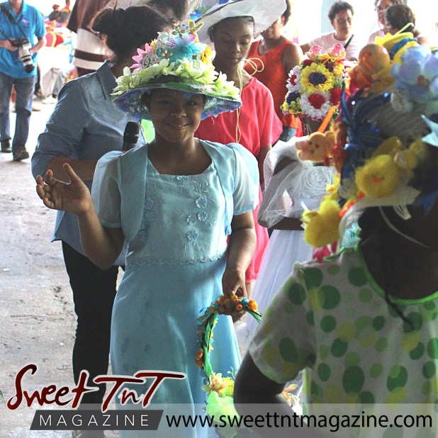 Girl in blue dress waving, with flowered bonnet and basket at special needs children Easter Bonnet parade at Queen's Park Cricket Club, color eggs, Sweet T&T, Sweet TnT, Trinidad and Tobago, Trini, vacation, travel