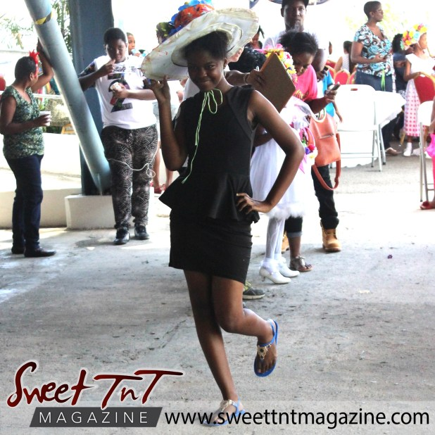 Teenage girl in short black dress holding flowered bonnet, and blue and gold sandals, at special needs children Easter Bonnet parade at Queen's Park Cricket Club, color eggs, Sweet T&T, Sweet TnT, Trinidad and Tobago, Trini, vacation, travel
