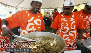 Chefs of Dockers crew cooking curried duck in big pot at cook-out wearing orange t shirts and aprons with white hats with ducks in Sweet T&T, Sweet TnT Magazine, Trinidad and Tobago, Trini, vacation, travel