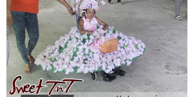 Special needs girl on wheelchair pink flowers models at Easter Bonnet parade at Queen's Park Cricket Club, disney characters on umbrella, Sweet T&T, Sweet TnT, Trinidad and Tobago