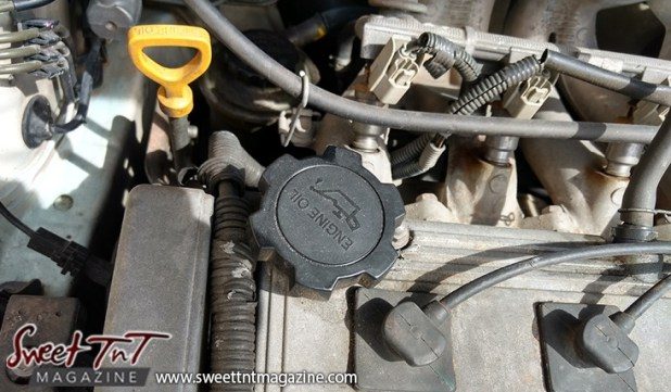 Engine of car, dip stick, oil cap, for car care tips article, in sweet T&T for Sweet TnT Magazine, Culturama Publishing Company, for news in Trinidad, in Port of Spain, Trinidad and Tobago, with positive how to photography.