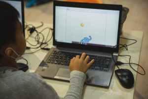 crop ethnic schoolboy typing on laptop in classroom