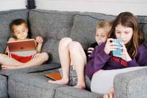 New normal: Children lying on sofa and using gadgets.