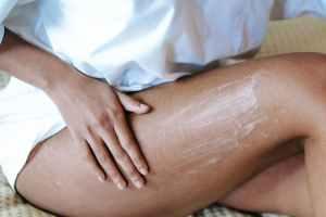 CBD cream. Woman massaging leg with lotion in bedroom.