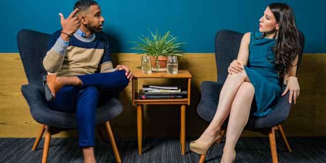 Get smart. Woman wearing teal dress sitting on chair talking to man