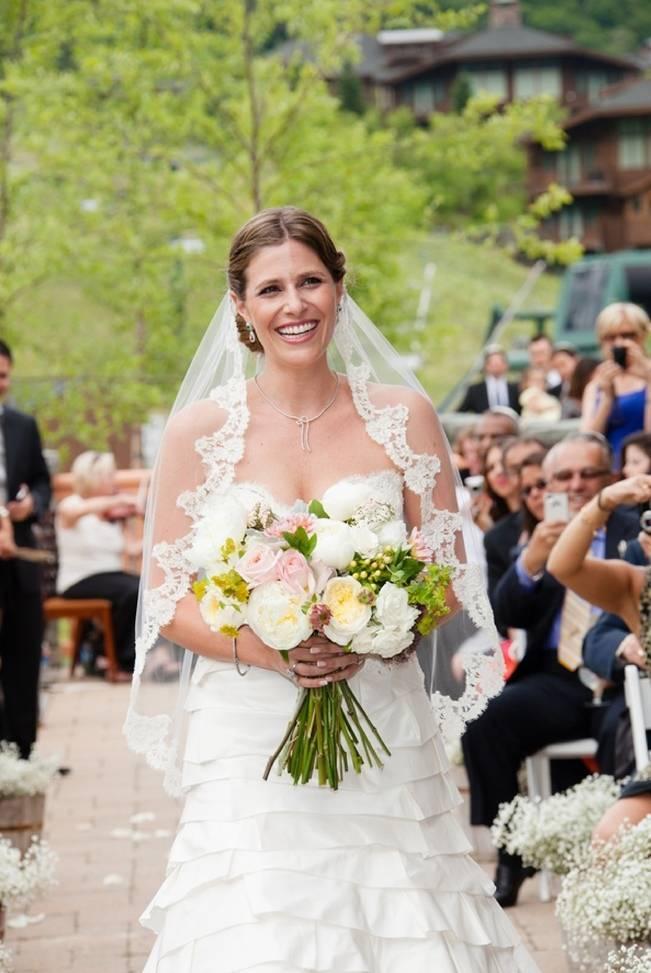 bride walking down outdoor wedding aisle