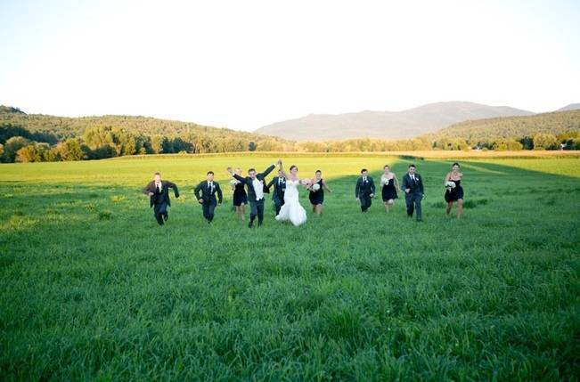wedding party running through a field